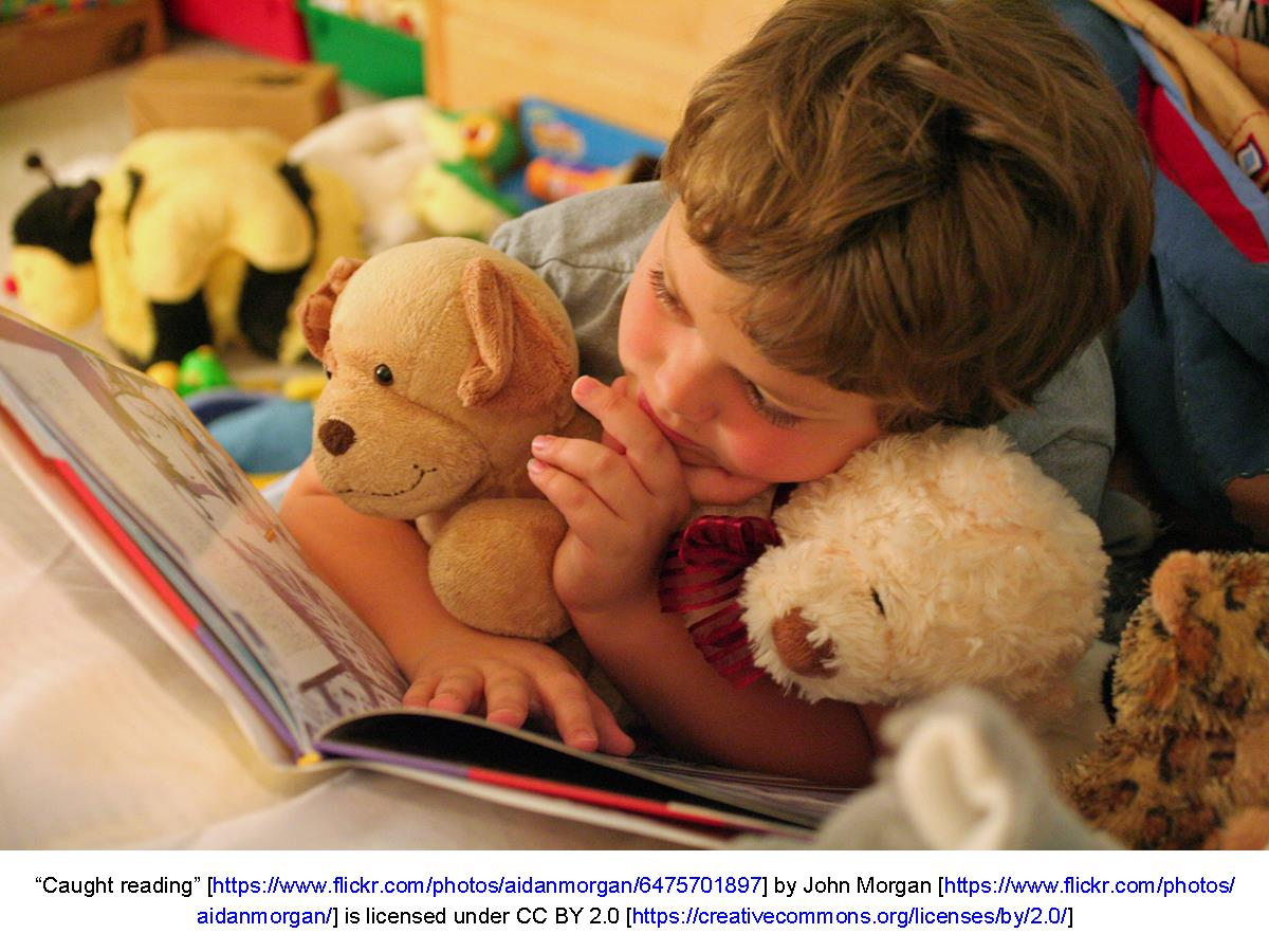 Child reading book with stuffed animal toys