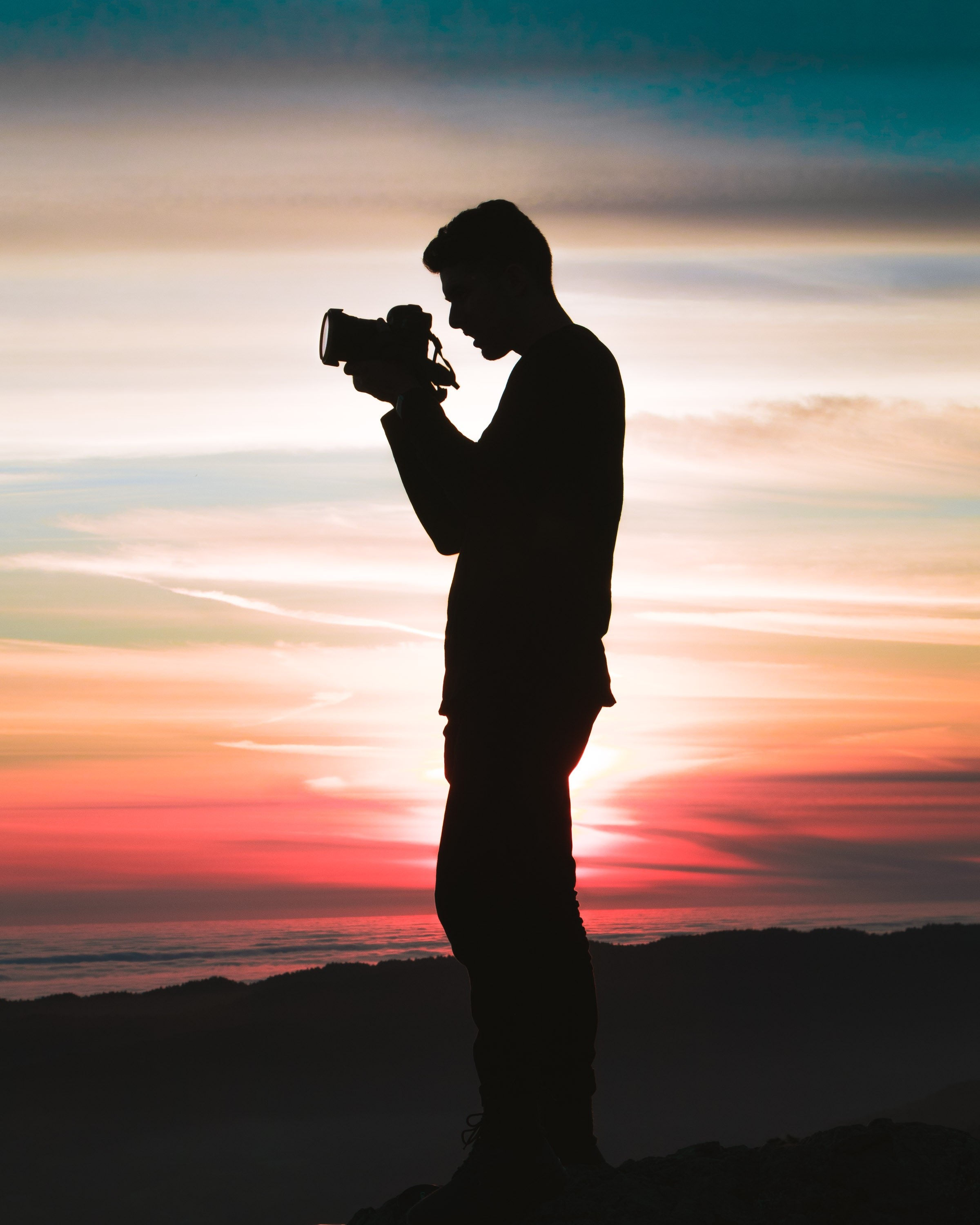 Silhouette of man with manual camera against a sunset