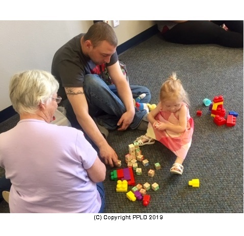 Child with adults playing with Duplo blocks