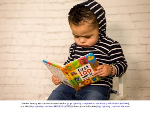 Toddler reading book and looking serious