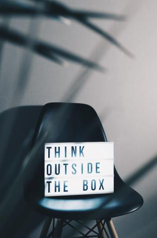 "Chair with a sign that says ""think outside the box."""