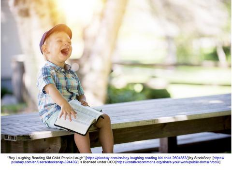 Child reading a book and laughing