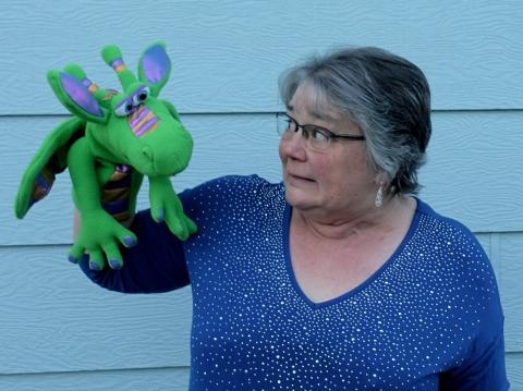 person holding green dragon puppet