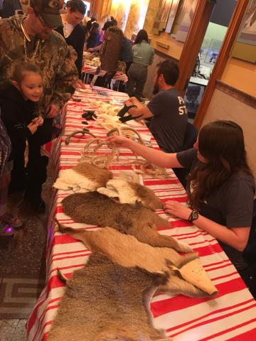 Children gathered around table laden with animal skins and skulls